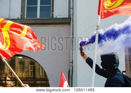 STRASBOURG FRANCE - APR 20 2016:Man holding smoke grenade as hundreds of people demonstrate as part of nationwide day of protest against proposed labor reforms by Socialist Government