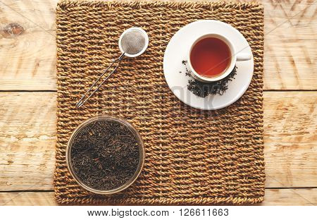 Morning cup of tea on a wooden table on straw napkin with tea strainer and jar of loose tea - mockup