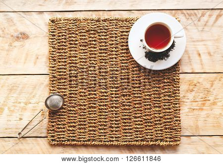 Morning cup of tea on a wooden table on straw napkin with tea strainer - mockup ** Note: Soft Focus at 100%, best at smaller sizes