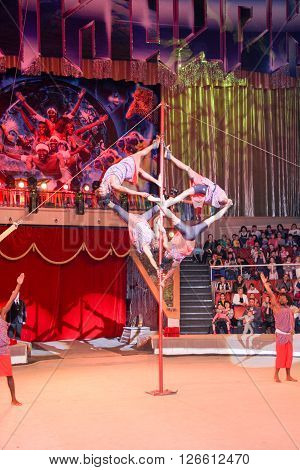 LUGANSK , UKRAINE - APRIL 9, 2016: several acrobats in a circus performance on the pole.