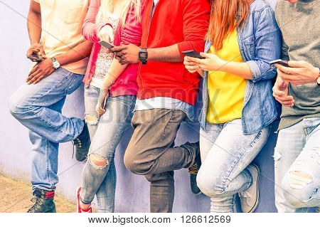 Multiracial group of friends texting sms and looking down to cell phone - Interracial students hands using mobile - Concept of young people addiction to web technology - Focus on hand of red hair girl