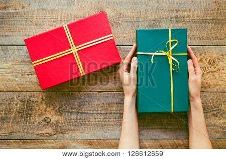 green gift box in girl hands  and red box on old brown wooden table