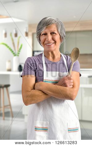 Happy friendly senior woman or Granny baking in the kitchen in her apron standing with folded arms holding a wooden spoon smiling at the camera