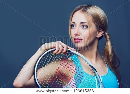 young woman with a tennis racket, against grey studio background