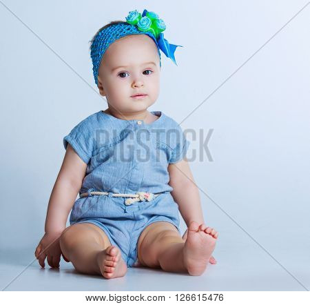 beautiful one year old baby against blue studio background