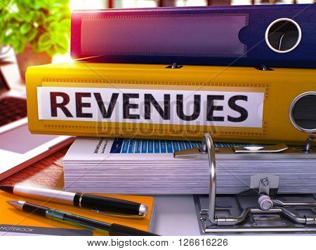 Yellow Ring Binder with Inscription Revenues on Background of Working Table with Office Supplies and Laptop. Revenues - Toned Illustration. Revenues Business Concept on Blurred Background. 3D Render.