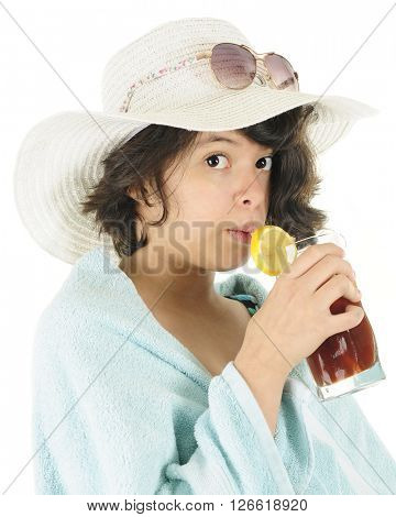 Close-up of a pretty young teen ready for the beach in her swim suit, towel, beach hat and sunglasses.  She's looking at the viewer as she sips on her iced tea.  On a white background.