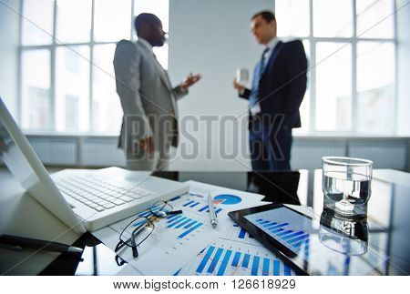 Two businessmen talking in office at table with laptop, touchpad and financial documents