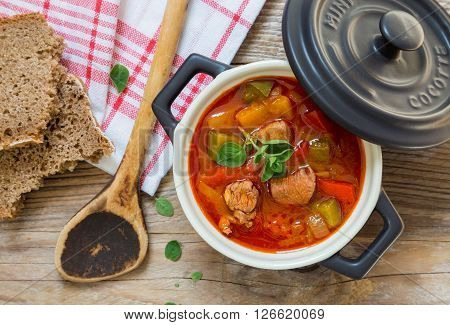 Goulash In A Black Cocotte With Marjoram On Rustic Wood