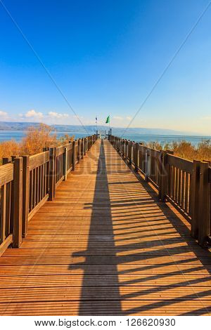 Wooden pier leading to the famous Sea of Galilee. Sunset on the lake of Kinneret