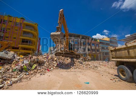 Portoviejo, Ecuador - April, 18, 2016: Heavy machinery picking rubble from destroyed buildings after tragic and devastating 7.8 earthquake in city center.