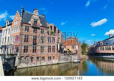 Ghent, Belgium - April 12, 2016: View of old colorful traditional houses along the canal in popular touristic destination Ghent, Belgium.