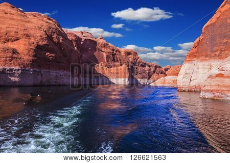 The foamy trace from powerboat crosses emerald waters. Hills from red sandstone surround the lake. The lake Powell on  river Colorado