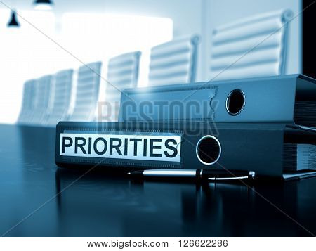 Priorities - Business Concept on Toned Background. Priorities - File Folder on Wooden Office Desk. Toned Image. 3D Rendering.