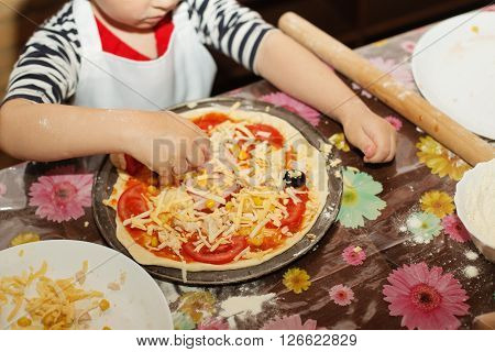 Children make pizza. Master class for children on cooking Italian pizza. Young children learn to cook a pizza. Kids preparing homemade pizza. Little cook.