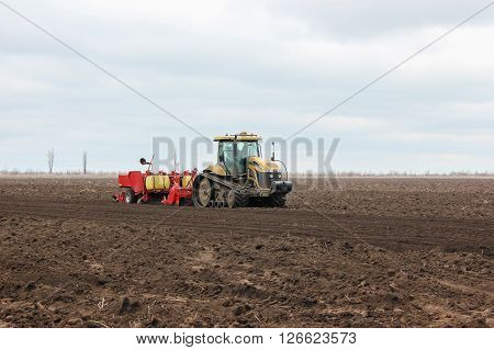 Modern Tractor On Soil Treated Cultivator In The Field