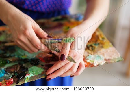 The Girl Artist Holding A Palette With Oil Paints, Brush And Palette Knife