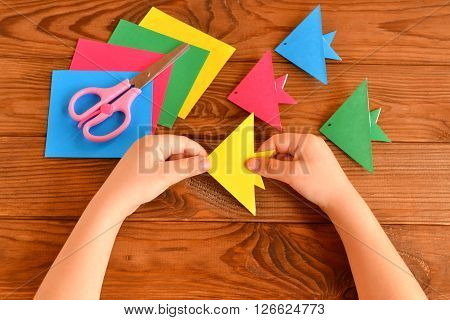 Origami colorful fish, paper sheets, scissors. Child holds an yellow origami fish in his hands. Brown wooden background