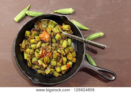 Indian Bhindi masala or okra fry in a cast iron pan with copy space on a wooden moosy background.