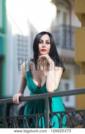 Black haired woman in the green dress is watching from the porch