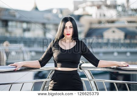Gothic woman on the modern steel porch in the black costume