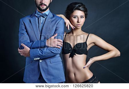 Beautiful lady in bra with handsome guy in suit. Young couple is hugging each other. Portrait of girl in underwear and boy indoors in passionate pose. Beauty woman with attractive lace lingerie