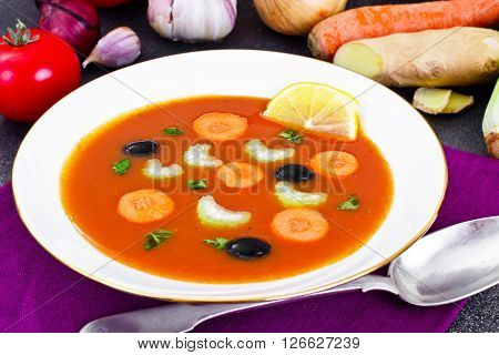 Carrot Tomato Soup in Plate. Behind lie on the soup ingredients, vegetables. National Italian Cuisine. Studio Photo