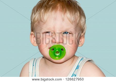 Funny baby grimaces. Studio photography on a blue background.