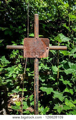 Old rusty metal cross in a cemetery forgotten grave