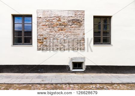 Modern white street wall with some small windows and example of old brickwork