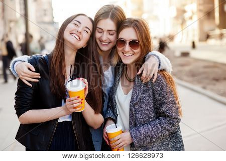Three young women, best friends smiling at the camera