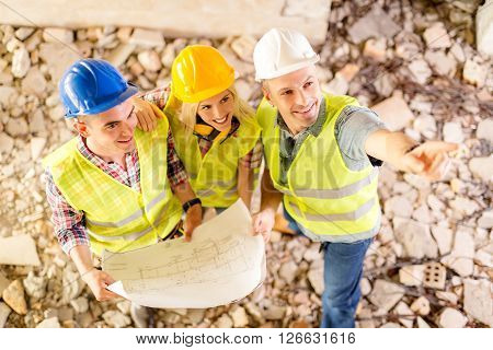 Three construction architects review plan in building damaged in the disaster.