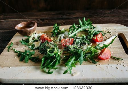 Salad on a wooden board salad of arugula arugula and tomato arugula salad with tomatoes and parmesan salad on a wooden board salad on a brown background salad with sesame seeds