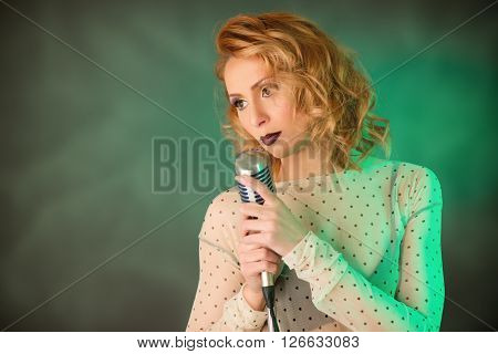 Beautiful retro female singer holding a vintage microphone with stand and singing ballad.
