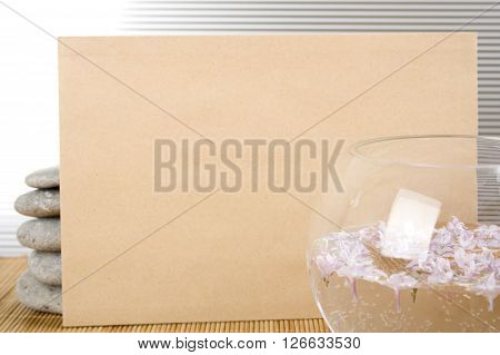 Against the background of rocks and the bowl with water and flowers, a clean sheet of brown paper