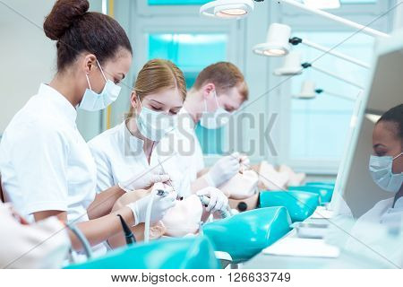 Three dentistry students working together in team on phantom