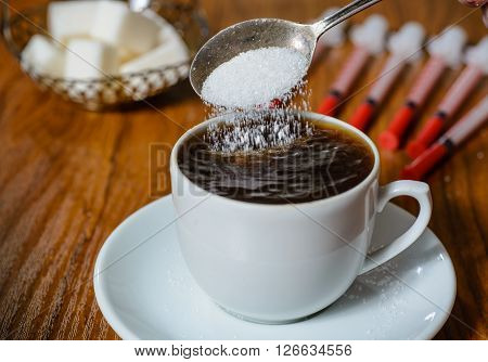Close-up: a teaspoon with sugar falling into a Cup of coffee. Amid the chunks of sugar and syringes for insulin