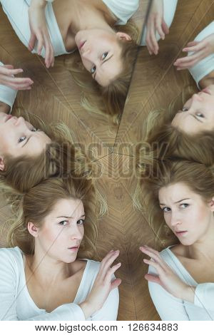 Young woman lying on wooden floor by the mirror wall looking anxiously at the camera surrounded by her multiple reflections