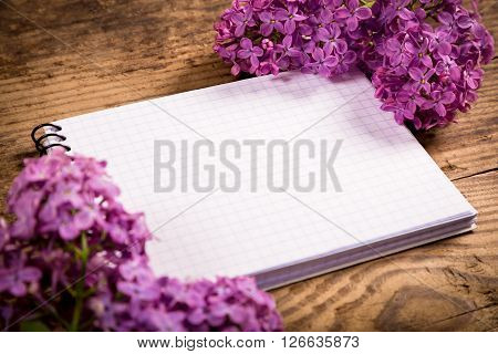 Bunch of lilac on brown wood old table with blank notebook, empty space for text