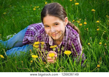Cute girl lying on field of dandelions, outdoor shooting