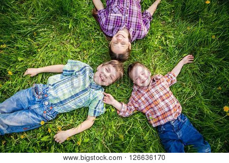 Three dreaming kids lying together on the green grass with dandelions, outdoors