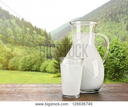 Pitcher, glass of milk on wooden table against forest and mountain background