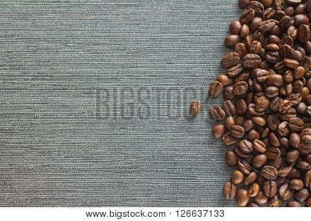 Coffee beans on grey tile background copy space