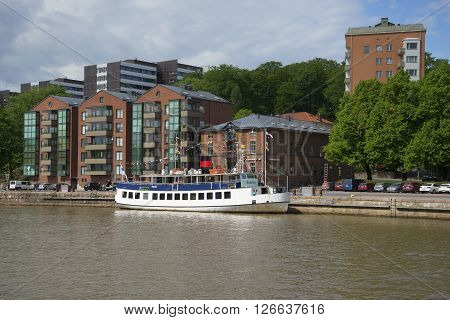 TURKU, FINLAND - JUNE 13, 2015: The modern embankment of the river Aura on a summer day. Tourist boat moored to the pier in Turku, Finland