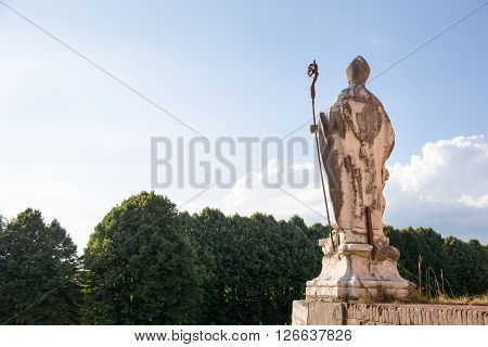 Ancient statue of a bishop holding a staff. Placed atop the medieval wall that surrounds the Tuscan village of Lucca Italy. Seen from behind and looking at copy space in the sky.