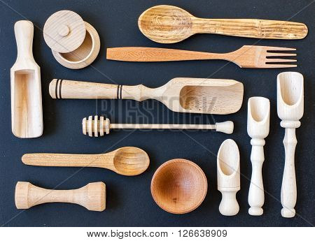 Set of the wooden kitchen utensils on black wooden background. spoon mortar kitchen spatula rolling pin bowl fork. Overhead view of wood utensils on black wood board background.