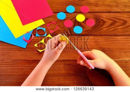 Children hands holding the scissors and paper and cut out the circle. Sheets of paper, paper circles on a brown wooden background