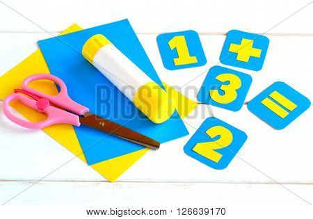 Paper cards with numbers, scissors, paper sheets, glue on a white background