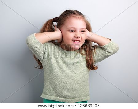 Cute fun kid girl coverd ears the fingers and gesturing that not want to listen on blue background with empty copy space
