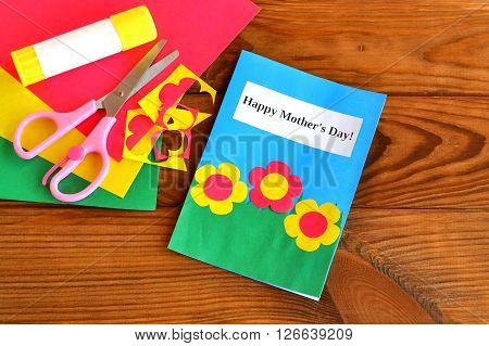 Greeting card Happy mother's day - children crafts. Scissors, glue, paper scraps, paper sheets on brown wooden background
